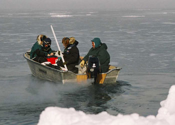 Photograph of researchers boating into a sea ice lead to collect samples