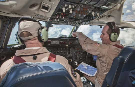 Photograph of pilots flying a DC-8 aircraft during Hurricane Karl