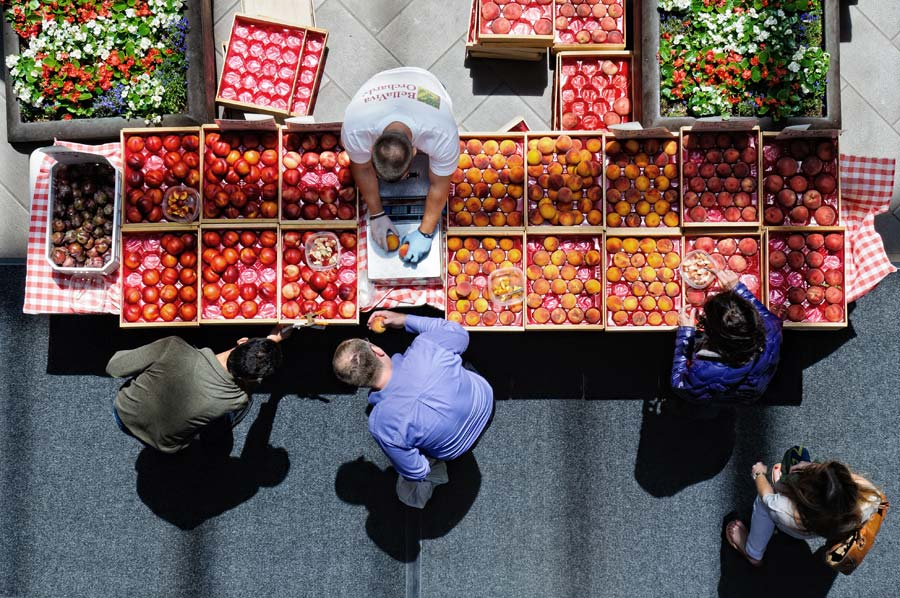 Photograph of a farmer selling produce at a California farmers market