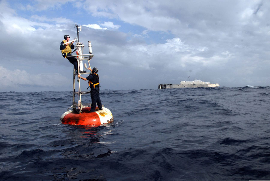 Photograph of Navy Minemen adjusting a buoy