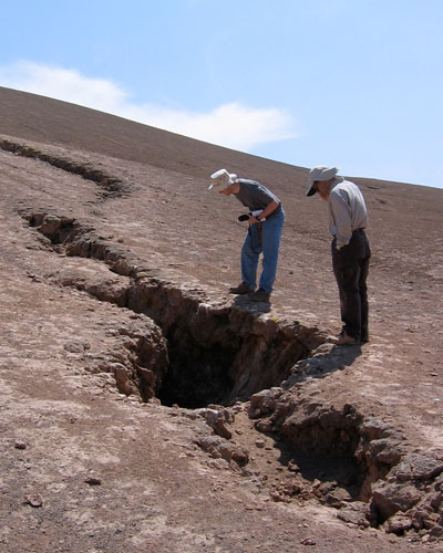 Photograph of scientists examining a large crack caused by an earthquake